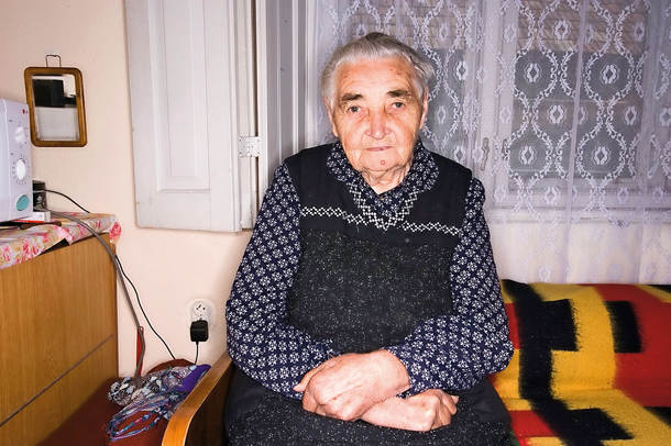 Old woman with a serene expression sitting on the bed with hands crossed  on her lap