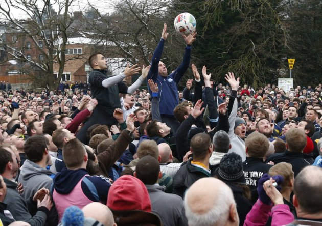 The ball is thrown into the hug to start the annual the annual Shrovetide football match in Ashbourne