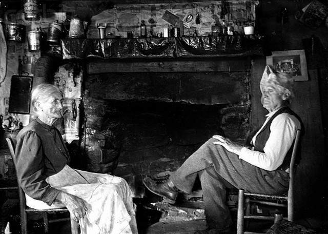 early 20th century --- Elderly Couple Sitting by Fireplace --- Image by © CORBIS